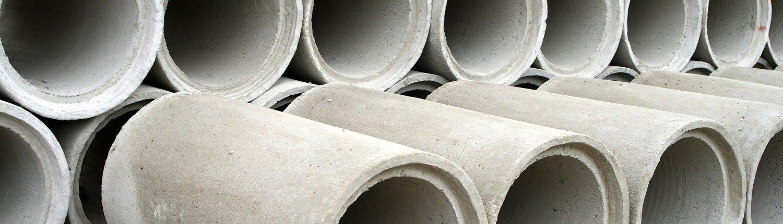 In einer Reihe gestapelte, graue Betonrohre.