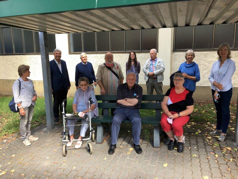 Mitglieder der Seniorenvertretung und des Fördervereins sowie weitere Personen auf und hinter der Sitzbank