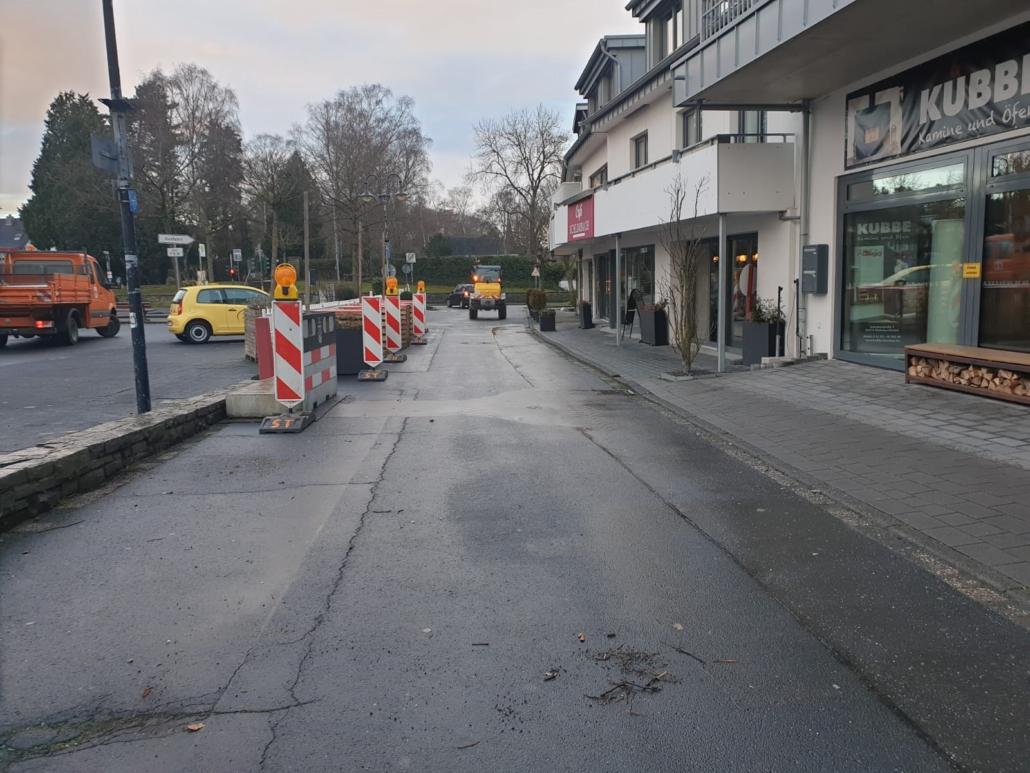 Eine Straße führt auf eine Kreuzung zu.Rechts befinden sich Geschäfte. Auf der linken Seite stehen Absperrungen, daneben befindet sich ein asphaltierter Parkplatz. Dort steht ein gelbes Auto.