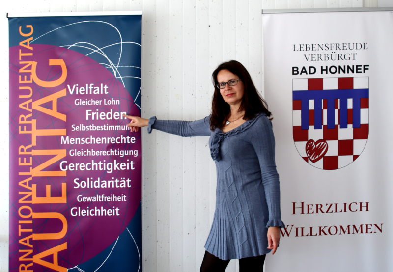 Gleichstellungsbeauftragte vor dem Rollplakat zum Weltfrauentag des Vereins Gleichberechtigung und Vernetzunges