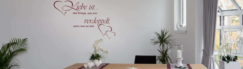 """Ansicht des Trauzimmers im Rathaus. Im Mittelpunkt ein Tisch mit zwei Plätzen für das Brautpaar und gegenüber der Stuhl des Standesbeamten. An der Rückwand ein Zitat: """"Liebe ist das Einzige, was sich verdoppelt, wenn man es teilt."""""""