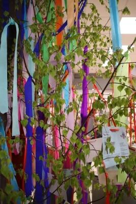 Zweige eines Maibaums mit bunten Flatterbändern - Karten mit Ehrenamtsangeboten aufgehängt