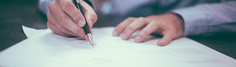 Männliche Hände halten einen Kugelschreiber über einem Stapel Formularen, Bild ist leicht verschwommen
