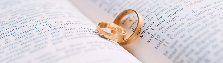 Aufgeschlagenes Buch mit hineingelegten Eheringen