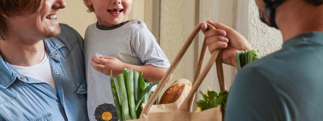 Ein Fahrradkurier überreicht einem Mann eine mit grünem Gemüse gefüllte Einkaufstasche aus Jute. Der Mann steht im Türrahmen seiner Wohnung und trägt sein Kind auf dem Arm. Das kleine Kind lächelt den Fahrradkurier an.