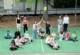Die Klasse 4a der Grundschule sitzen auf dem Schulhof - die Erwachsenen stehen.