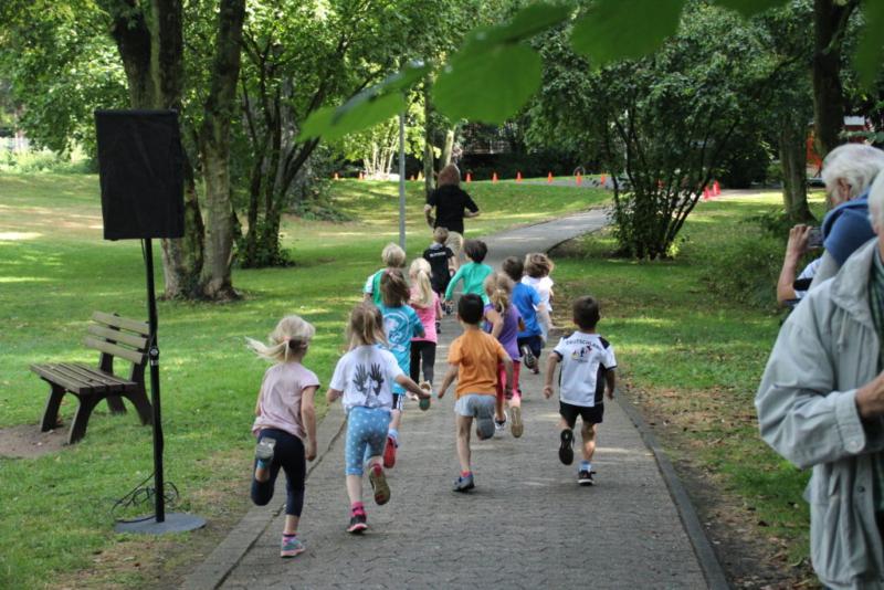 Kinder rennen in einer Parkanlage über einen gepflasterten Weg.