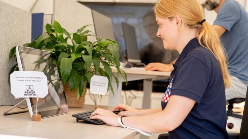 Eine junge Frau sitzt an einem Bürotisch und schaut auf einen Bildschirm