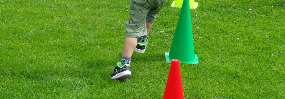 Kleines Kind rennt im Slalom um grüne und rote Pylone auf einer grünen Wiese