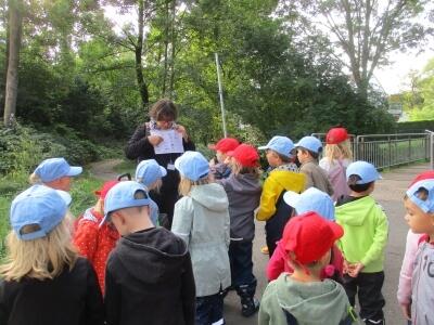 Projektleiterin Maria-Elisabeth Loevenich zeigt den Kindern ein Prospekt.