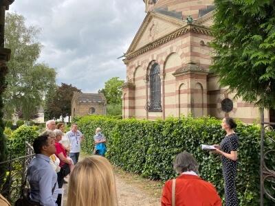 Personen die vor dem Mausoleum stehen und der Vorleserin Catrin Möderler zuhören