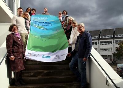 Auf der Treppe vor dem Rathaus halten die Netzwerksmitglieder die Fahne für die Auszeichnung #BNE2030