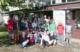 Gruppenbild: Im Schulgarten vor der Schule die Kinder der 4. Klassen und Erwachsene
