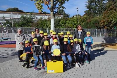 auf dem Schulhof vor der Theodor-Weinz-Grundschule die Schulklassen mit gelben BHAG-Kappen mit Lehrerein, Schulleiterin und Projektleiterin