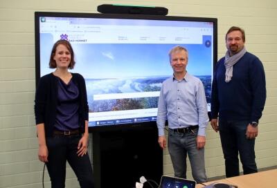 Drei Perssonen vor dem Monitor mit Foto von Bad Honnef - vom Drachenfels aus fotografiert
